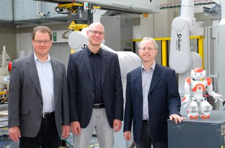"""Drei Professoren und ein Nao im Robotiklabor: Prof. Dr. Dirk Rokossa, Prof. Dr. Siegmar Lampe und Prof. Dr. Clemens Westerkamp, Sprecher (v.l.) leiten das neu gegründete Kompetenzzentrum """"I4os - Industrie 4.0 Osnabrück"""" an der Hochschule Osnabrück / Foto: Hochschule Osnabrück"""