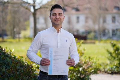 Faruk Güler, geboren und wohnhaft in Wertheim am Main, freut sich, seine Bachelorurkunde in Händen zu halten