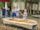 Nachbau eines Einbaums. Museumsbesucher testen die Nachbildungen der bronzezeitlichen Werkzeuge. Zweite von rechts die Archäologin Vera Edelstein / Copyright: Pfahlbaumuseum Unteruhldingen