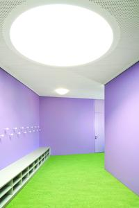 Der Eingangsbereich ist von der fliederfarbenen Garderobenwand und dem in der Komplementärfarbe Grün gehaltenen Fußboden geprägt. Der Linoleumfußboden zieht sich als verbindendes Element in die Klassenzimmer hinein