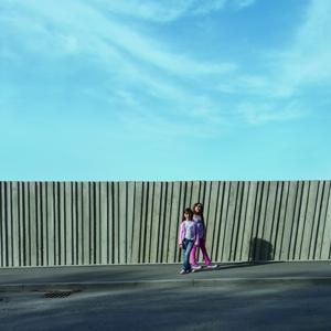 Straßenseitig ist die schalungsraue Betonfassade des Schulneubaus als strukturreiche Mauer zu sehen, über die man ins Tal blicken kann