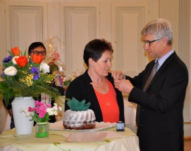 Geschäftsführer Bernhard Wehde steckt Frau Beate Hammel die Ehrennadel des Christophsbads zum 40-jährigen Dienstjubiläum persönlich an. Im Hintergrund links zu sehen ist Pflegedirektorin Birgit Gambert
