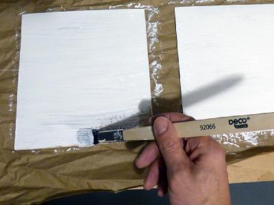 Dünne Holzplatten, weiß matt wie die Rahmen lackiert, ersetzen die eingeschobenen Plexiglasscheiben, damit Ständer für Werbeflyer angebracht werden können.