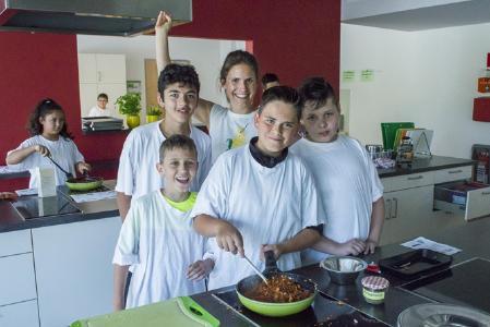 """Bei der """"Aktion Pflanzen-Power"""" kochen Kinder in einer Münchner Schule pflanzliche Gerichte mit der vegan-Bloggerin Stina Spiegelberg (hinten Mitte)."""