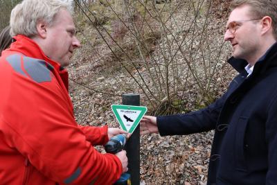 Thomas Gärtner (li.) und Dezernent Dr. Jens Mischak beim Aufstellen des Schildes: Es werden erstmals Pfosten aus recyceltem Kunststoff verwendet, die Naturdenkmalschilder enthalten zusätzlich das Vogelsberg-Logo und das Datum der Verordnung