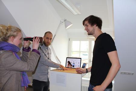 """Die MID-Studenten Lucas Köhler (links) und John Moss erklären einer Ausstellungsbesucherin in Osnabrück, wie ihr digitales Fernglas """"Itto"""" funktioniert"""