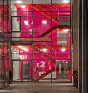In der Abenddämmerung verleiht die Beleuchtung den roten und purpurfarbenen mit Amphibolin beschichteten Flächen in diesem Treppenhaus einen besonderen Charakter mit hohem Aufmerksamkeitswert