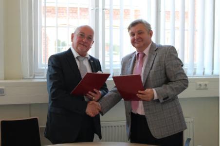 TH-Präsident Prof. Dr. László Ungvári (l.) und Vizedekan Tomasz P. Olejnik tauschen die unterzeichneten Dokumente aus