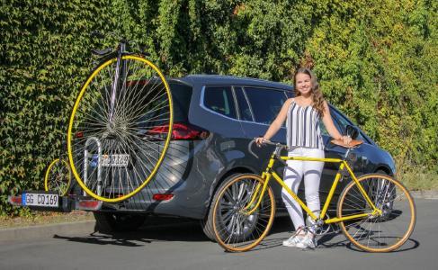 Große Fahrradtradition: Der neue Opel Zafira mit dem Hochrad von 1886; davor das Rennrad von 1935 mit den damals üblichen Holzfelgen
