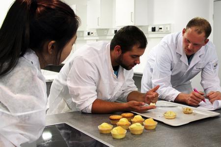 Juyoung Kim, Sven Sackewitz und Philipp Hilker überprüfen den Geschmack und die Konsistenz ihrer selbstgebackenen Muffins. Ihre Kommilitonen müssen im Anschluss bewerten, welche Muffin-Rezeptur am besten schmeckt.