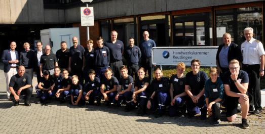 Die jungen Workshop-Teilnehmer, Lehrmeister und Einsatzkräfte der Feuerwehr gemeinsam mit dem Überraschungsbesuch