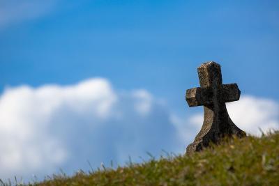 Kreuz auf einer Wiese vor blauem Himmel.