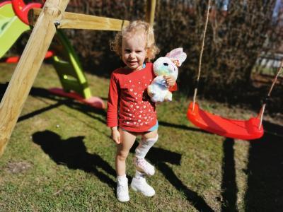 Kleines blondes Mädchen im Garten mit einem Plüsch-Oterhasen