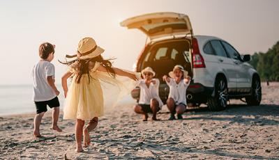 Familie am Strand vor Auto mit geöffneter Heckklappe
