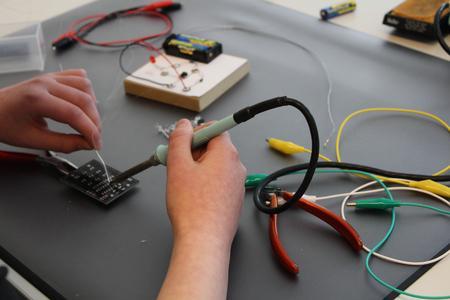 Die Mädchen beginnen mit der Herstellung ihres magischen Würfels mit dem Löten eines Computerchips