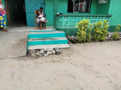 Frau mit Kind sitzt auf einer Holzveranda