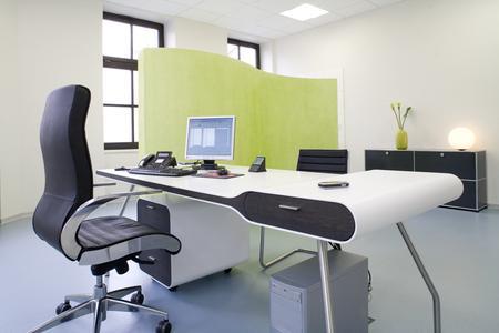 Hinter dem grün geschwungenen Paravent können sich die Patienten im Behandlungszimmer Aus- oder Ankleiden. Er bildet einen Blickfang in dem sparsam aber sehr stilvoll eingerichteten Raum.