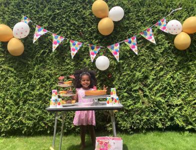 Fermosi steht im Garten hinter einem Tisch mit Kuchen, an der Hecke hinter ihr hängen Luftballons.