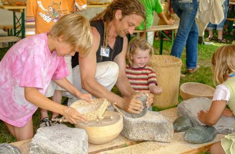 Museumsbesucher im Pfahlbaumuseum beim Getreide mahlen mit einem steinzeitlichen Mahlstein / Copyright: Pfahlbaumuseum Unteruhldingen