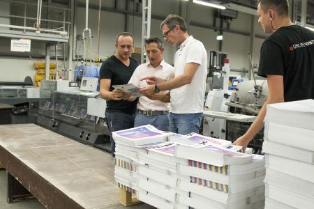 As one of the first print shops in Europe, Onlineprinters successfully certified its postpress operations. Armin Schörghofer (2nd from right), Ugra auditor, examines brochures in postpress together with co-auditor Thomas M. Schnitzler. (Bild: Onlineprinters GmbH)