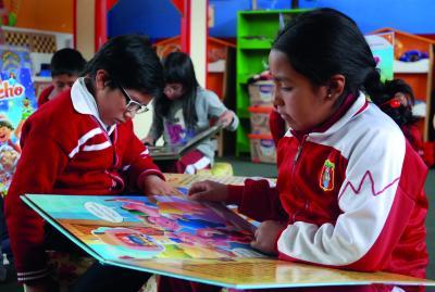 Peruanische Kinder beim gemeinsamen Lesen Copyright World Vision