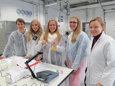Laboringenieurin Jessica Wiertz (rechts) zeigt den Oberstufenschülern, wie sie den pH-Wert ihres Apfelsaftes bestimmen können