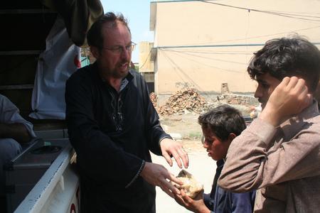 Shelter Now-Direktor Udo Stolte bei der Verteilung von Essensrationen an Flutopfer in Pakistan