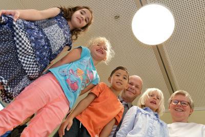 Amanda, Elise, Kim und Greta freuen sich mit Martin Schulze, Geschäftsstelle Umwelt Unternehmen, und Kita-Leiterin Urte Hahn-Reeschke, dass es im Kindergarten Drachenkinder jetzt deutlich heller ist. Denn durch die Unterstützung des Klimafonds konnte die Beleuchtung auf LED umgestellt werden