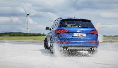 Heckansicht eines blauen Audi SQ5 bei Ausweichtraining auf nassem Skid-Pad.