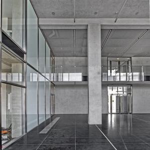 In der Eingangshalle setzt der glänzende Natursteinboden in Anthrazit einen dunklen Akzent zu den grauen und weißen Wandflächen