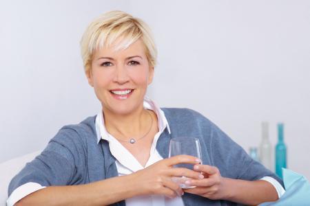 Frau mit Heilwasserglas - Eine Heilwasser-Trinkkur hilft beim Fasten