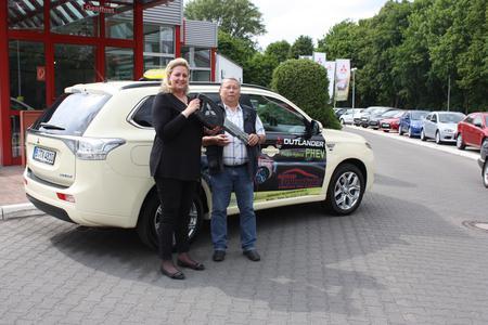 Mitsubishi Händlerin Gaby Breitenwischer gibt den symbolischen Schlüssel an den Berliner Taxifahrer Ottfried Rennebarth