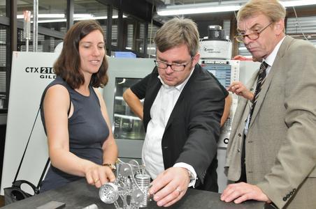 Dorothea Kliche-Behnke, Martin Rosemann und Harald Herrmann begutachten einen Stirlingmotor, den angehende Feinwerkmechaniker in der überbetrieblichen Ausbildung in Tübingen bauten (Foto: Handwerkskammer)