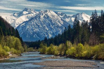 Auf dem Allgäuer Hauptkamm liegt noch Schnee, während beim Auwaldsee bei Fischen im Allgäu schon Frühling ist