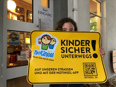 Kind mit Notinsel-Plakat