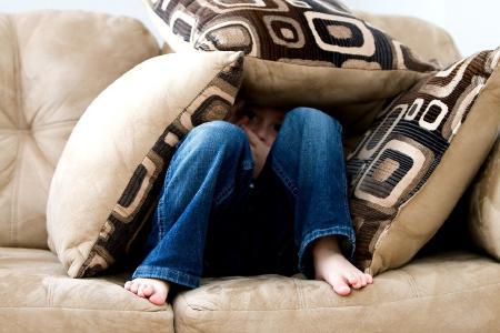 Kind auf der Couch unter Kissen versteckt. Foto: ambermb