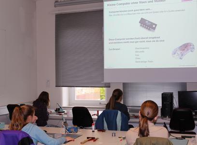 """Die Mädchen hören im Workshop """"Der magische Würfel"""" gespannt den allgemeinen Informationen über Computer und Stromkreise zu"""