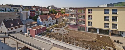 Eine Fußgängerbrücke (im Vordergrund) führt von der Altstadt direkt zu den Stadthäusern des modernen Wohnquartiers, Foto: Caparol Farben Lacke Bautenschutz/Martin Duckek