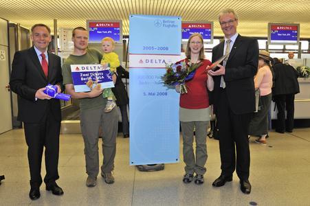 Thomas Brandt, Geschäftsführer Delta Air Lines Deutschland (rechts), und Flughafenchef Dr. Rainer Schwarz (links) hießen den Jubiläumsfluggast Anja Heinrich mit ihrem Mann Sören und Sohn Caio nach der Ankunft in Berlin willkommen
