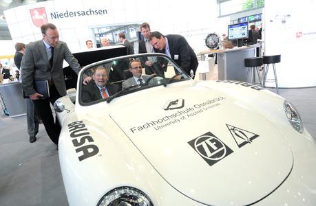 Spritztour über die Hannover Messe: Prof. Dr. Norbert Austerhoff (rechts) erklärt Tobias Schmidt (Wigos), Landrat Manfred Hugo und  Ansgar Pohlmann (Wigos) die Besonderheiten des neuen Elektrofahrzeugs