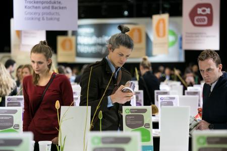 Prüfende Blicke am Neuheitenstand: Rund 700 Produkte präsentieren Aussteller aus knapp 100 Ländern in diesem Jahr bei den Messen Biofach und Vivaness in Nürnberg. Foto: obx-news/NürnbergMesse