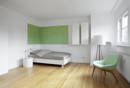 Studio 4: Die um die Ecke geführte Farbfläche betont den Schlafplatz. Die gelbgrüne Fläche bezieht sich auf die Schrank- und Fensterhöhe (Foto: Caparol Farben Lacke Bautenschutz/Blitzwerk und Fotograf Thomas Ott)