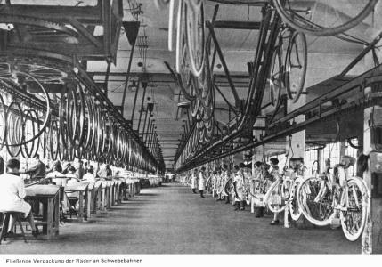 Fahrradmontage: 1927 transportieren Schwebebahnen einzelne Räder und fertige Modelle durch eine Opel-Produktionshalle
