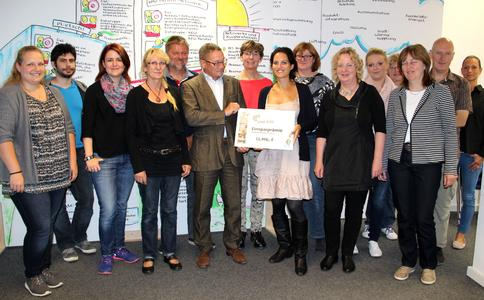 Sonja Kurtze, energiekonsens, und Hans-Georg Matthies, KiTa Bremen (Mitte), übergeben Prämien in Höhe von 11.460 Euro an 15 der teilnehmenden Kitas des Projektes ener:kita.