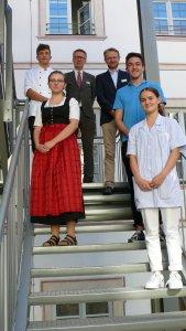 (Claudia Blank) zeigt die drei Auszubildenden Luis Kiebler (oben links), Isabella Bernard (2.v.l.) und Lisa-Marie Sturm (rechts) gemeinsam mit Dr. Stefan Raueiser, Markus Spies und Philipp Semer (v.l.n.r.) anlässlich des Einführungstages in Kloster Irsee