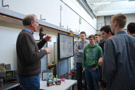 So macht Physik Spaß: Laboringenieur Martin Kröger (links) erklärt seinen Gästen vom Gymnasiums Bad Iburg, wo Elektromagnetismus uns im Alltag begegnet