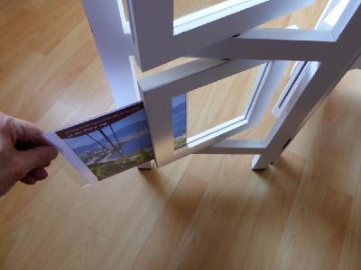 Zwischen zwei dünne Plexiglasscheiben lassen sich Bilder und Werbetexte in 360 Grad drehbaren Rahmen einschieben.
