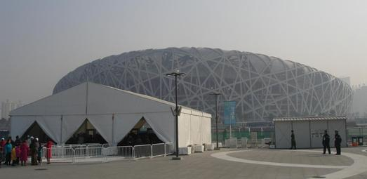 """Security-Zelte zur Eingangskontrolle auf dem Olympic Central Green vor dem olympischen Stadion """"Birdsnest"""" in Peking."""