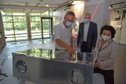 Geschäftsführer Dr. Kai Schiefelbein (links) mit Ministerin Dr. Carola Reimann am Lüftungsgerät, das speziell für den Einsatz in Klassenzimmern entwickelt wurde. Im Hintergrund Burkhard Max, Geschäftsführer der STIEBEL ELTRON-Tochtergesellschaft Tecalor, die das Gerät vertreibt