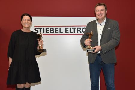 """Werbeleiterin Fátima Freitas und Pressesprecher Henning Schulz mit den beiden """"Oscars der Baubranche"""", die STIEBEL ELTRON in diesem Jahr gewinnen konnte in den Kategorien """"Regenerative Energien"""" und """"Lüftung und Klimatechnik""""."""